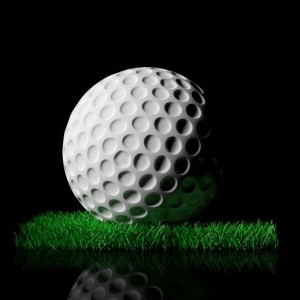 44877525 - golf ball on green turf patch, isolated on black background
